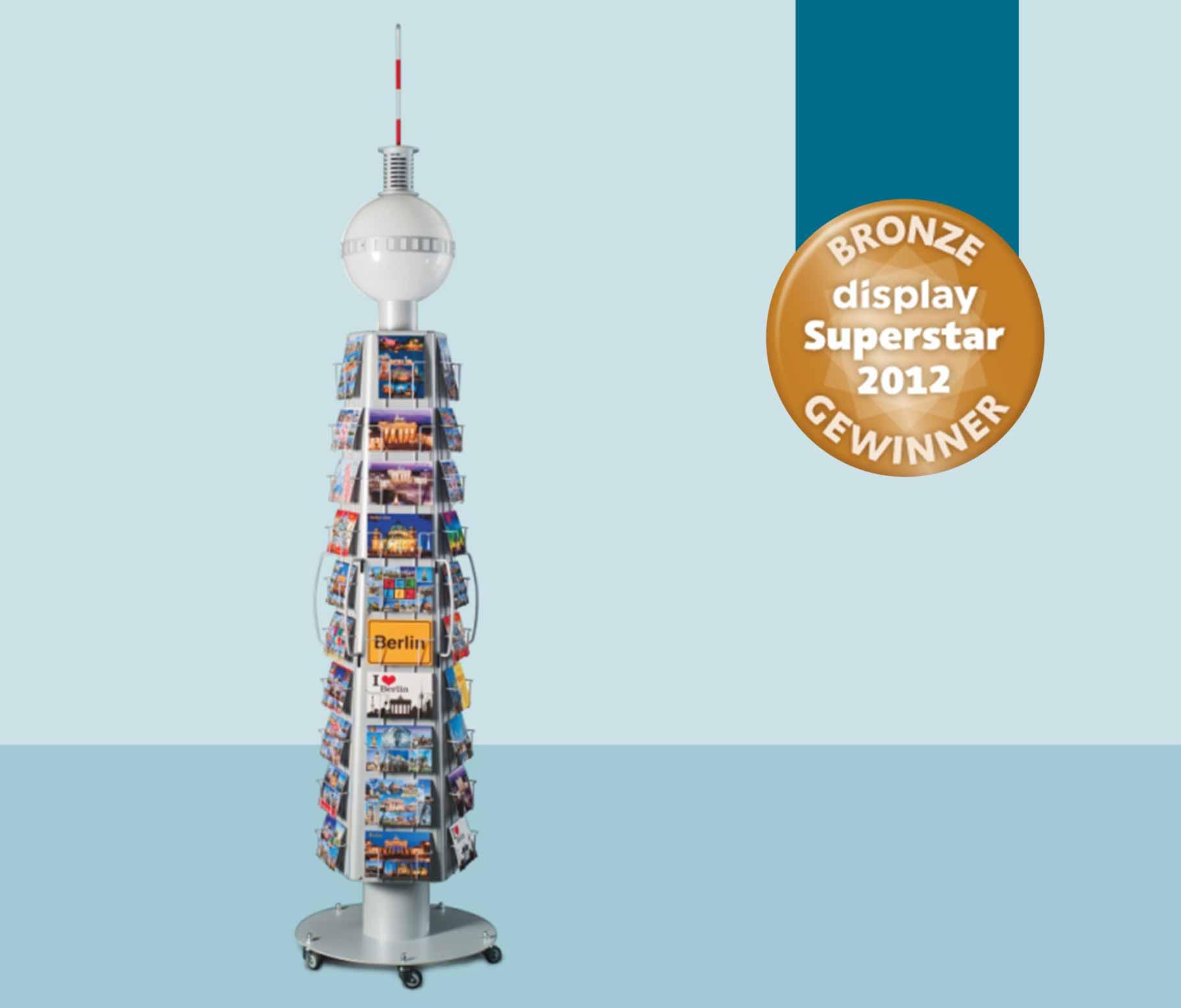 2012: Das Postkartendisplay für den Schikkus Verlag in Form des Berliner Fernsehturms wird mit dem Superstar in Bronze prämiert.
